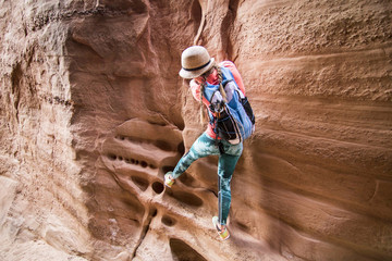 Woman climbing sandstone cliff, Grand Staircase-Escalante National Monument, Utah, USA