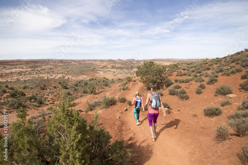 Two Women Hiking Through Desert At Grand Staircase Escalante