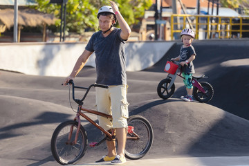 Man with boy with BMX bikes at skate park
