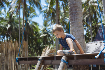Portrait of boy under palms