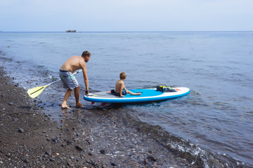 Father and son at sup surfboard,Bali,Indonesia.