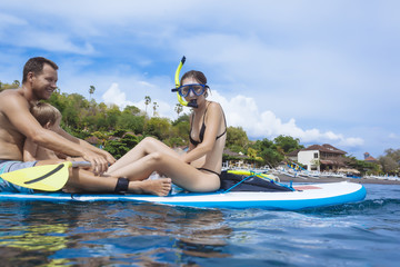 Family on sup surfboard in ocean,Bali,Indonesia