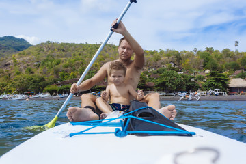 Father and son on sup surfboard,Bali,Indonesia.