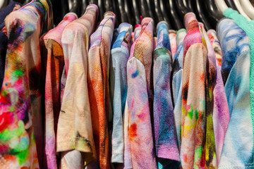 Close-up of colorful Clothes on black Plastic Hangers