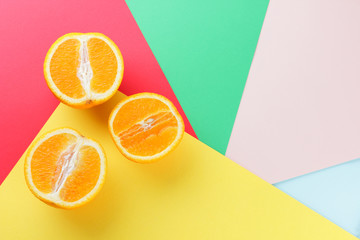 Fruits of oranges on a multicolored background, halves of oranges on colored paper. Citrus in the...