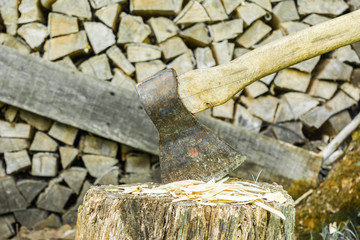 old ax is stuck in a stump against the backdrop of a woodpile, selective focus, abstract background
