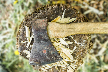 old ax lies on stump with chips, close-up abstract background