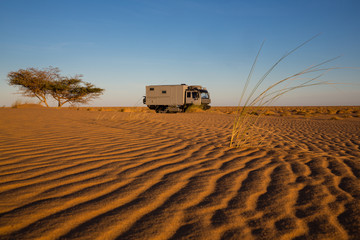 Dune camp with 4x4 expedition verhicle at a beautful sand dune in the Sahara