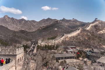 Beijing, China - April 28, 2010: Great Wall of China at Badaling. wide shot of the wall meandering over mountains with lots op people walking on top. Base and village up front. Blue sky.