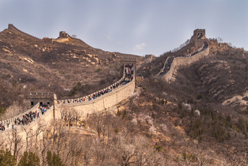 Beijing, China - April 28, 2010: Great Wall of China at Badaling. wide shot of the wall meandering over mountains with lots op people walking on top. Blue sky.