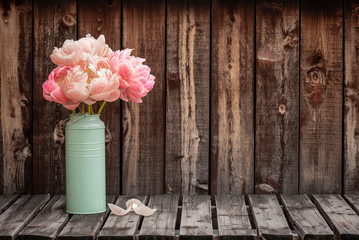 A bunch of pink peonies in a green vase on the left side of a rustic plank table leaving room for copy.