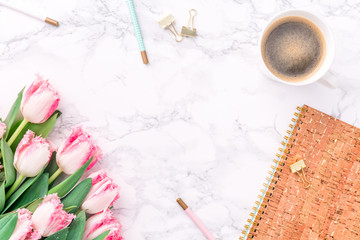 Pink tulips with festive stationary and coffee on white marble background. Feminine job, gender equality, home office and career concept. Copy space