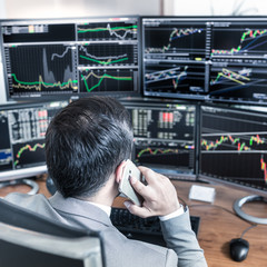 Over the shoulder view of computer screens ful of charts and data analyses and stock broker trading online.