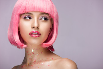 beautiful woman with pink hair and makeup with glitter looking away isolated on violet