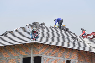Workers installing concrete tiles on the roof while roofing house