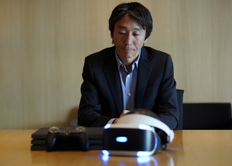 Sony Interactive Entertainment Inc CEO and President Kodera speaks behind a PlayStation 4 Pro (L) and PlayStation VR during a group interview in Tokyo