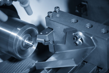 The CNC lathe machine or turning machine cutting the thread at the metal shaft part.Modern manufacturing process.