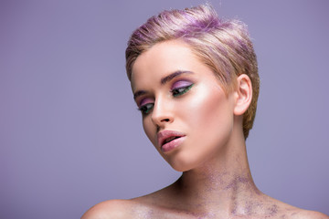 attractive woman with violet glitter on neck and short violet hair isolated on violet