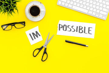 From impossible to possible. Do difficult task at work concept. Cutting the part im of written word impossible by sciccors. Office desk. Yellow background top view copy space
