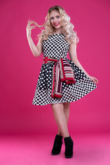 A beautiful happy girl in a polka-dot dress touches a strand of her blond hair. Girl with blond hair on an isolated pink background.