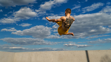 Tricking on street. Martial arts. Man makes high jump barefoot. Shooted from bottom foreshortening against sky.