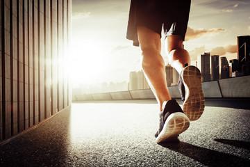Close up of runner legs run on the street . Sunrise morning scene .