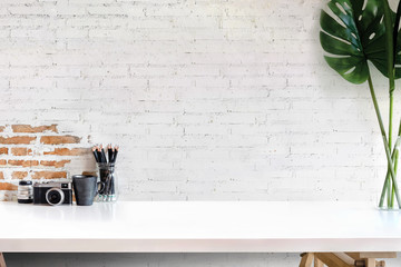 Loft workspace with photographer equipment on white wood table at home or studio.