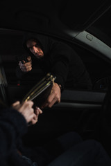 serious male thief aiming by gun and stealing bag from woman sitting in car