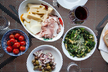 top view of mediterranean dishes: cheese, tomatoes, spinach, olives, sepia