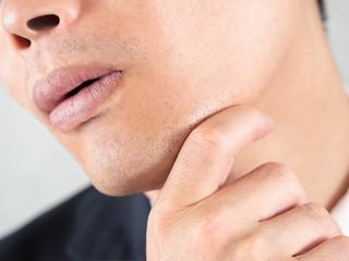 アゴヒゲの剃り跡を気にする男性ビジネスマン