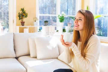 Happy young woman drinking coffee at home