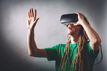 Young man using virtual reality headset on a solid background