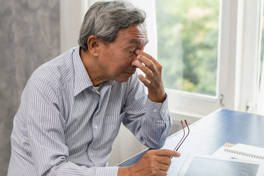 Asian elderly stress tired and holding his nose suffer sinus pain fatigue from hard work.