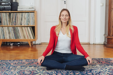 Attractive woman sitting meditating at home