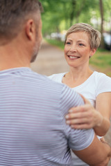 Smiling mature woman embracing man in park