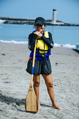 Young woman paddler smiling with an oar in hand