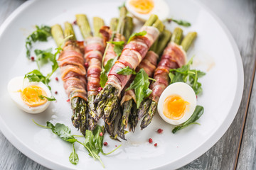Fresh asparagus wrapped in bacon  on a white plate with arugula tomatoes and eggs
