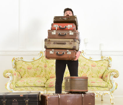 Macho elegant on surprised face carries pile of vintage suitcases. Man with beard and mustache wearing classic suit delivers luggage, luxury white interior background. Butler and service concept.