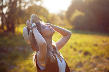 Cute charming girl in summer in the field. Young woman is happy and feels free outdoors