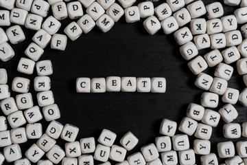 Word CREATE on wooden cubes on a black wooden table