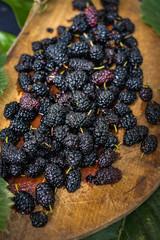 Black mulberry berries on wooden board. Organic farm sweet fruits of Georgia region. Sweet, juicy, delicious with antioxidant. Raw vegan vegetarian healthy food