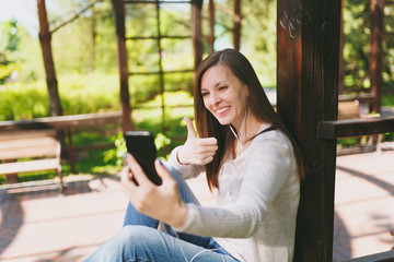 Portrait of beautiful woman wearing light casual clothes. Smiling female sitting in city park in street outdoors on spring nature, doing selfie shot on mobile phone or video call. Lifestyle concept.