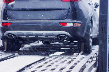 in winter, a lorry transports premium-class cars,