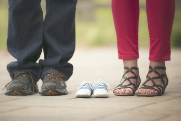 baby boy photo announcement with shoes of expecting parents