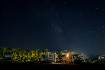 Campers parked by the sea at night under a starry sky. Summer night camping, lighted caravans and trees in the background. Stars illuminate the night, tourists camp outdoor in the nature.