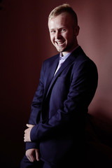 Portrait of smiling businessman on dark background