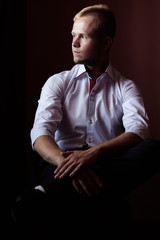 portrait of young successful businessman on dark background