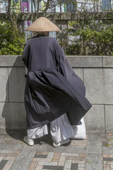 Monk with hat and traditional Japanese clothes blowing in the wind in central Tokyo, Japan