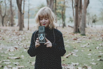Women photography standing and hand holding retro camera in outdoor.Vintage tone