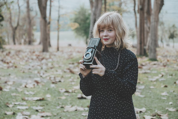 Women photography smilling,standing and hand holding retro camera in outdoor.Vintage tone